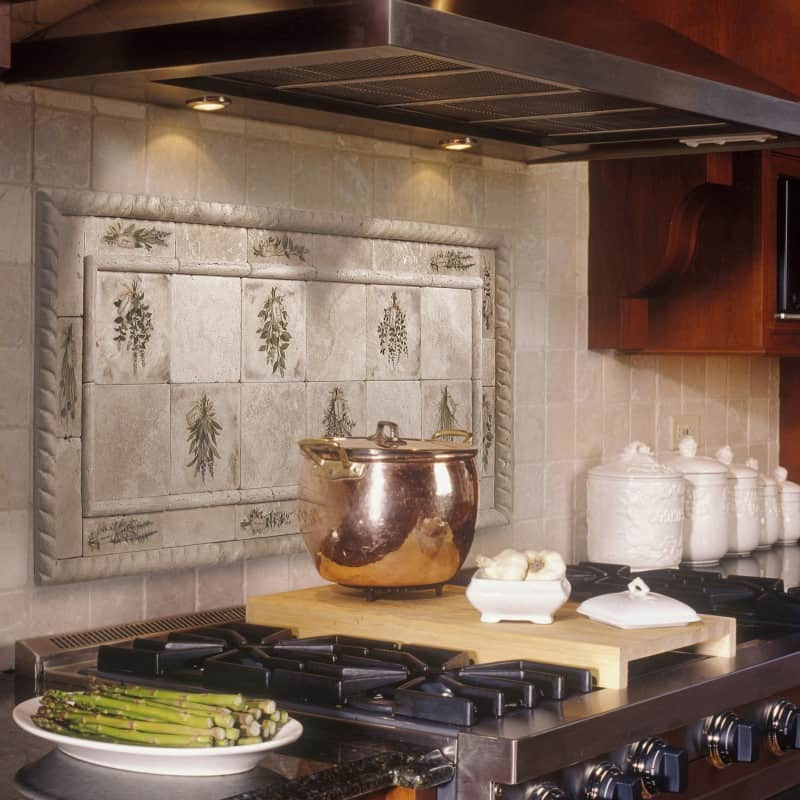 Kitchen with stainless steel commercial cook top and vent hood with gas burners, wood cutting board, copper pot, tile back splash, ceramic canisters, and plate of asparagus on counter